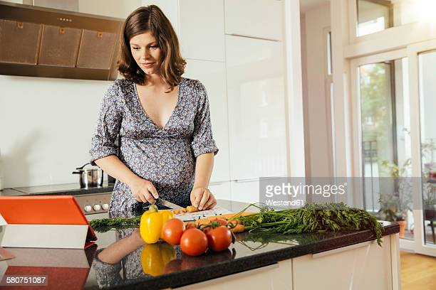 Pregnant woman cutting vegetables in her kitchen while looking at digital tablet