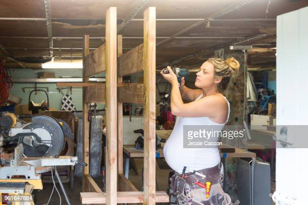 a pregnant woman does diy with a drill in a messy workshop - grossesse humour photos et images de collection