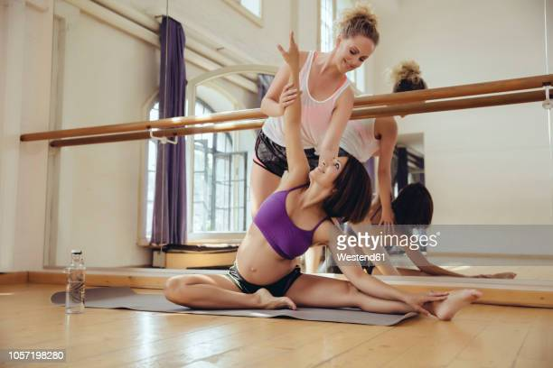 pregnant woman doing exercises with her personal trainer - barre class stock photos and pictures