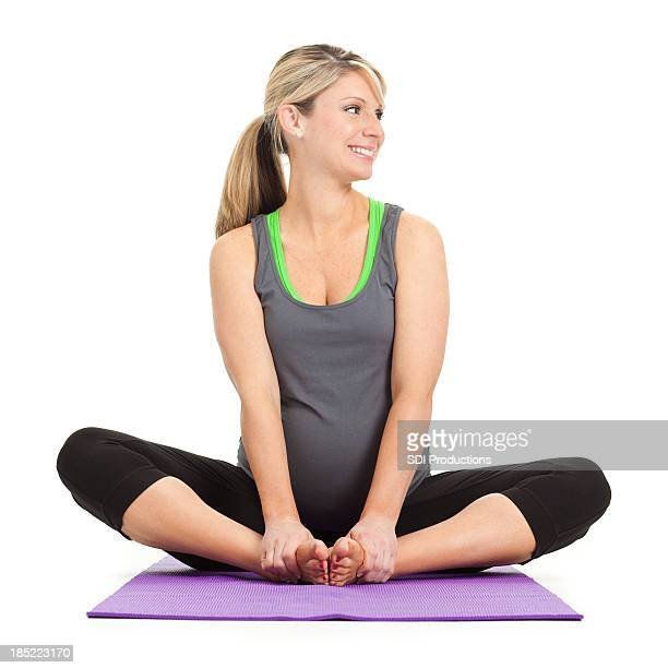 Pregnant woman doing stretches on exercise mat