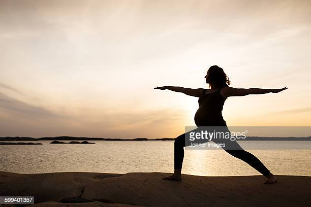 Pregnant woman doing yoga at sunset