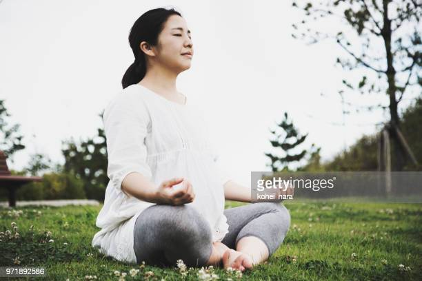 Pregnant woman doing yoga in the park