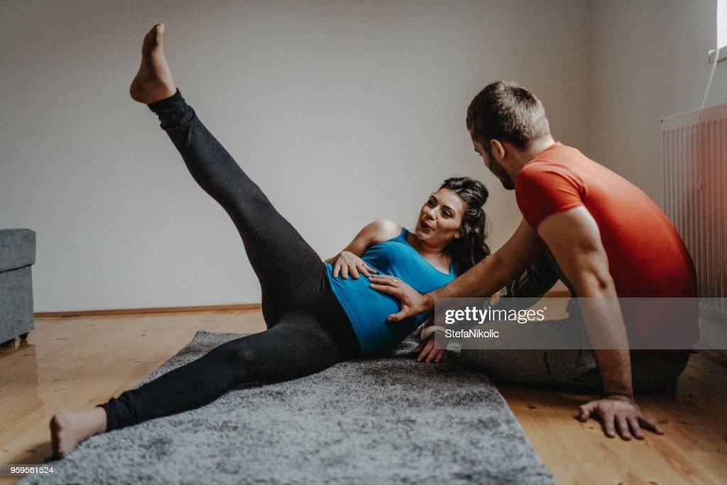 Schwangere Frau beim Yoga mit ihrem Ehemann : Stock-Foto