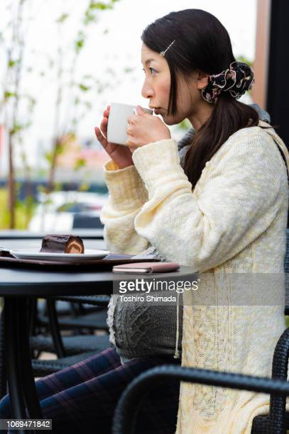 A pregnant woman drinking a cup of coffee