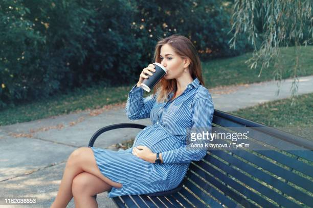 pregnant woman drinking coffee while sitting on bench at park - pregnant coffee stock pictures, royalty-free photos & images