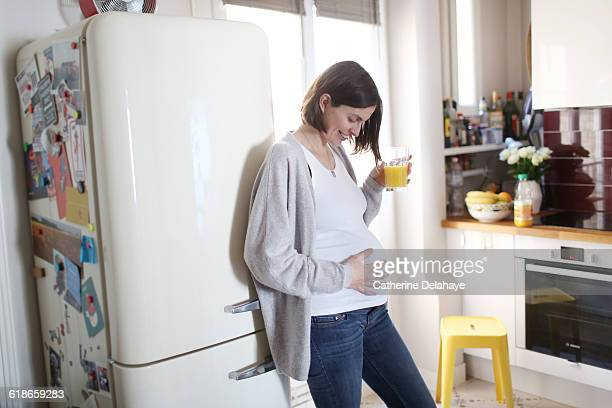 A pregnant woman drinking orange juice at home