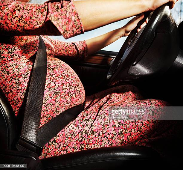 Pregnant woman driving car, side view, mid-section, close-up