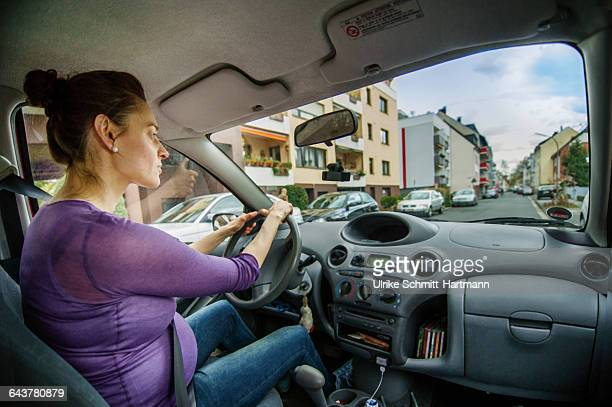 pregnant woman driving her car - purple shirt stock photos and pictures