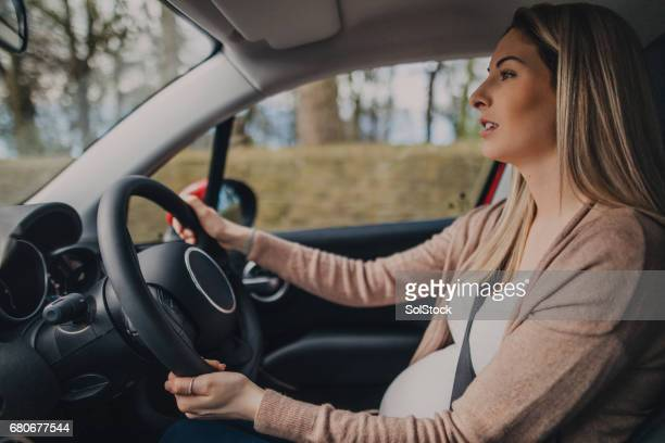 pregnant woman driving - driver stock photos and pictures