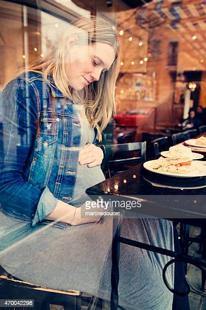 Pregnant woman eating alone at a restaurant holding belly.