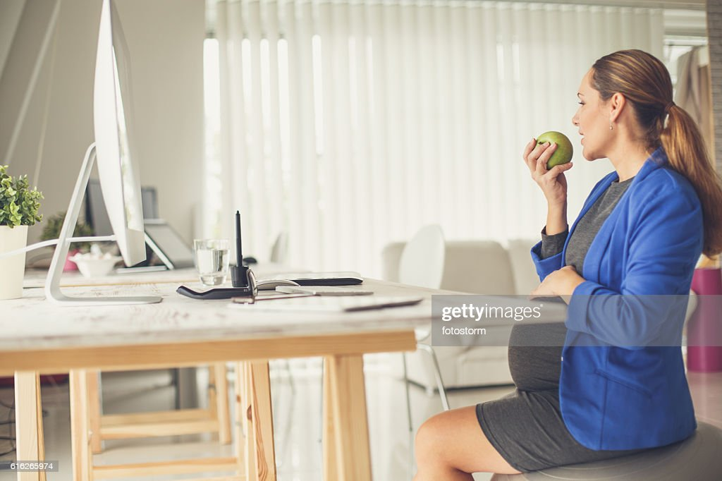 Pregnant woman eating apple at work : Stock Photo