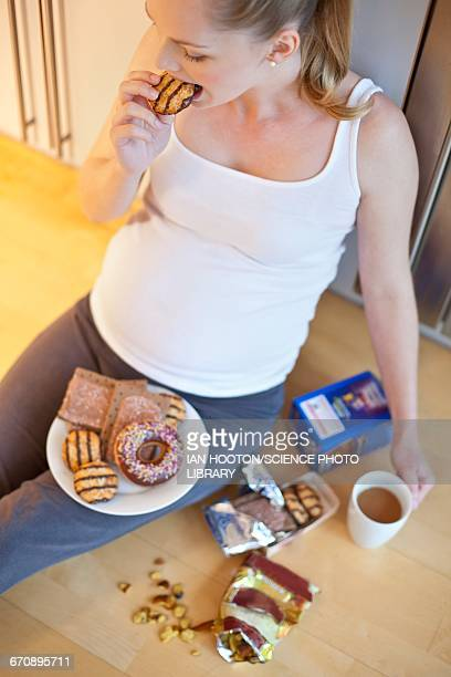 Pregnant woman eating biscuit