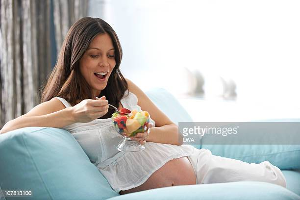 Pregnant Woman Eating Bowl of Fruit