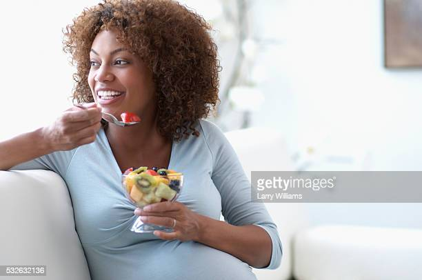 pregnant woman eating fruit salad on sofa - mid adult women stock pictures, royalty-free photos & images