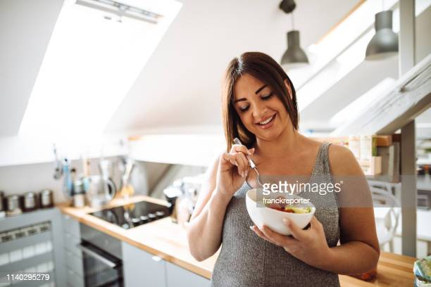 pregnant woman eating healthy food at home - overweight stock pictures, royalty-free photos & images