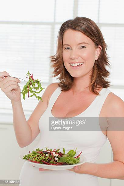 Pregnant woman eating salad in kitchen