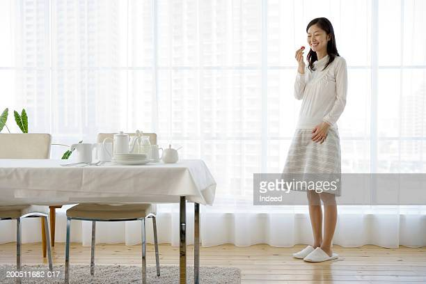 Pregnant woman eating strawberry at home, smiling, side view