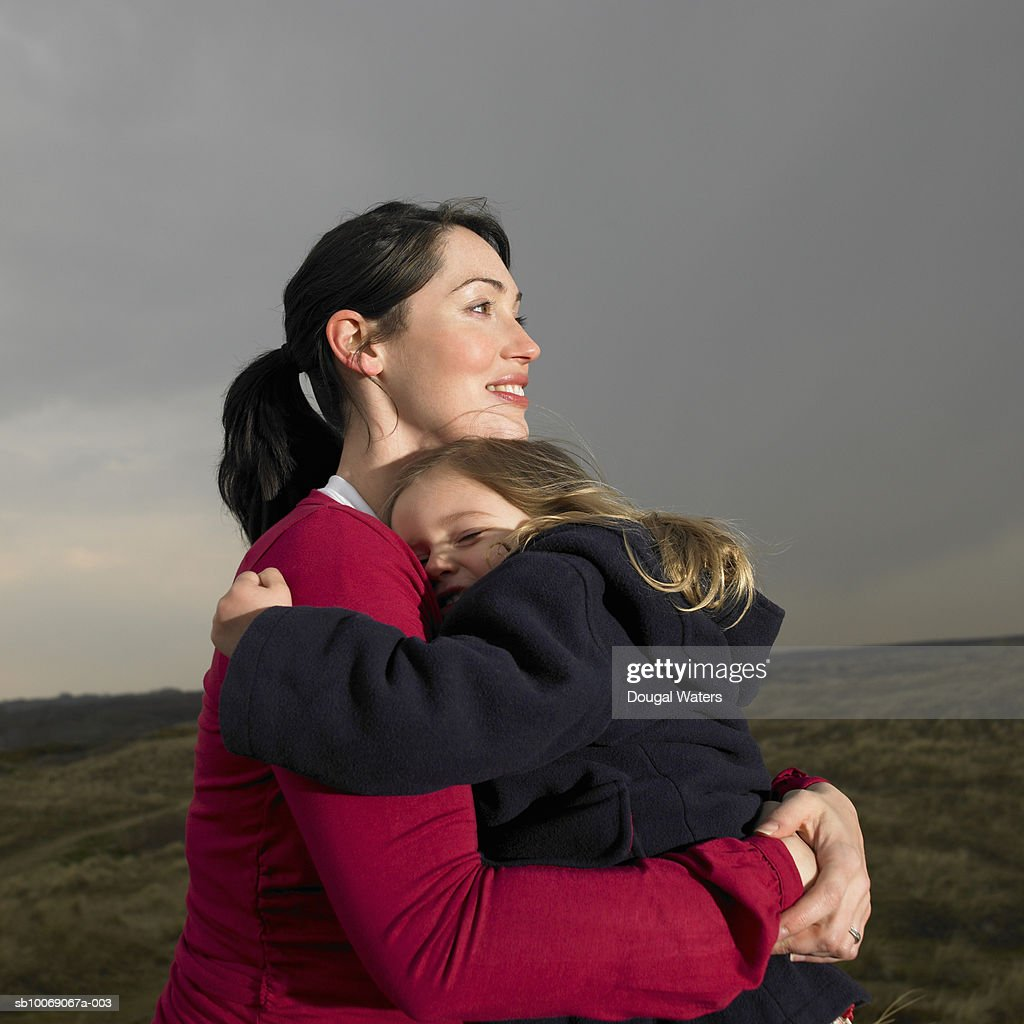 Pregnant woman embracing daughter (2-3) on heath land : Stockfoto