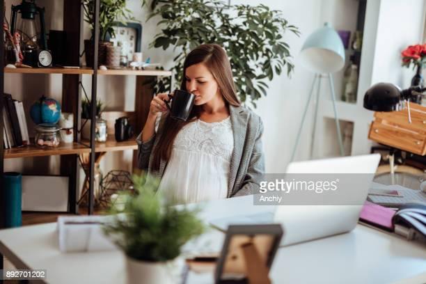 妊娠中の女性が彼女のオフィスでコーヒーを楽しむ - マタニティウェア ストックフォトと画像