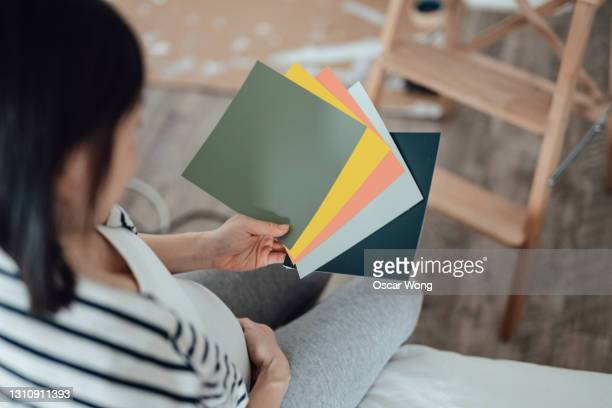 pregnant woman examining paint swatches for nurses room - verdict stock pictures, royalty-free photos & images
