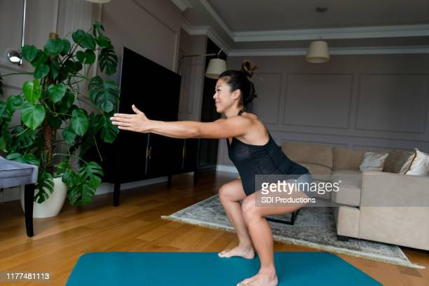 pregnant woman exercises in her home - squatting position stock pictures, royalty-free photos & images