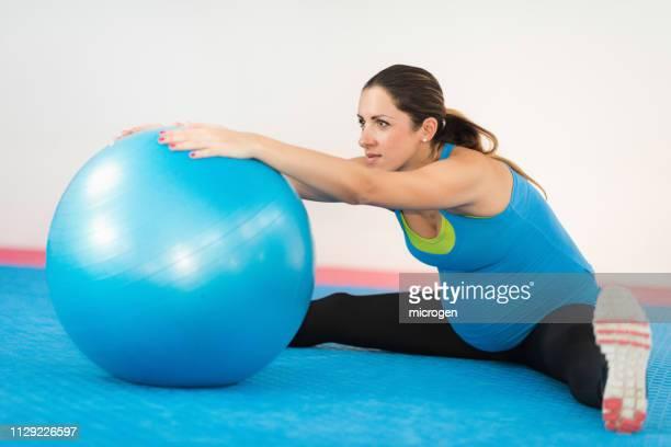 pregnant woman exercising with fitness ball in gym - geburtsvorbereitung stock-fotos und bilder