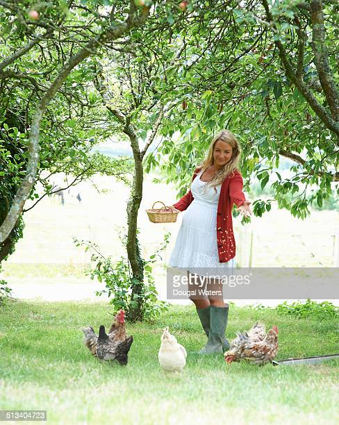 Pregnant woman feeding chickens in farmyard.