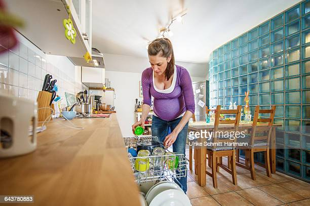 Pregnant woman filling dishwasher