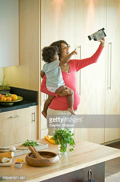Pregnant woman filming daughter (2-3) in kitchen with video camera