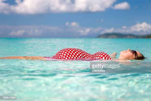 donna incinta galleggiare sull'acqua presso la spiaggia dei caraibi - costume da bagno foto e immagini stock