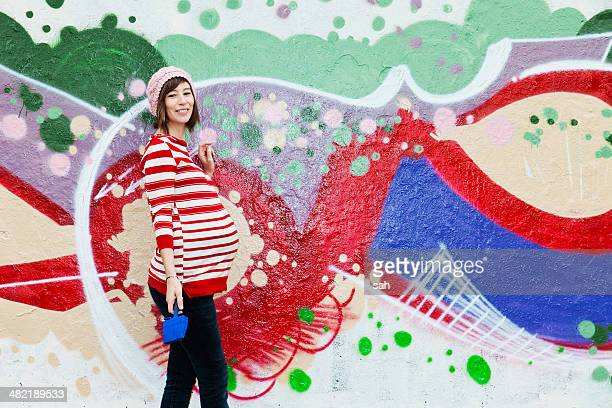 Pregnant woman, graffiti in the background