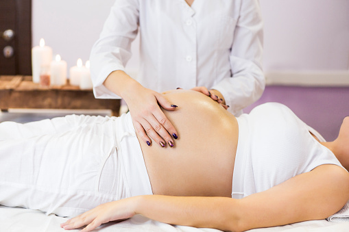 Pregnant woman have massage treatment at spa salon 955776958