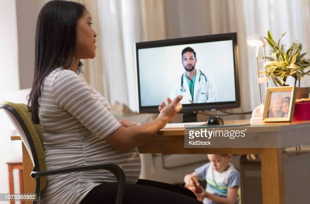 pregnant woman having a video call with her doctor - prenatale zorg stockfoto's en -beelden