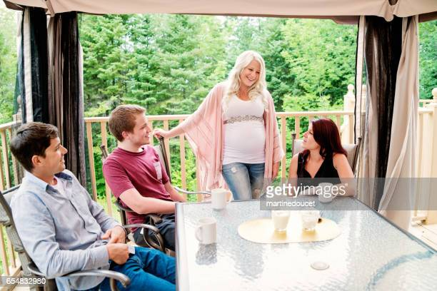 Pregnant woman having coffee with friends outdoors.