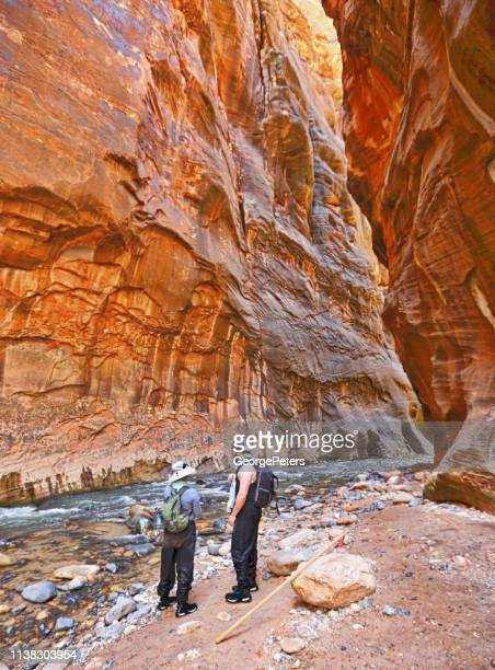Pregnant woman hiking the Zion Narrows with husband