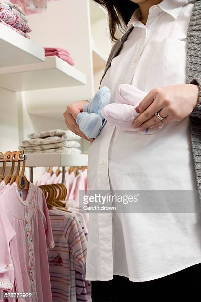 Pregnant Woman Holding Baby Booties