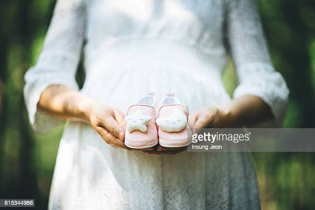 Pregnant Woman Holding baby's shoes in Front of Belly