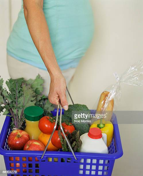 Pregnant woman holding basket of groceries