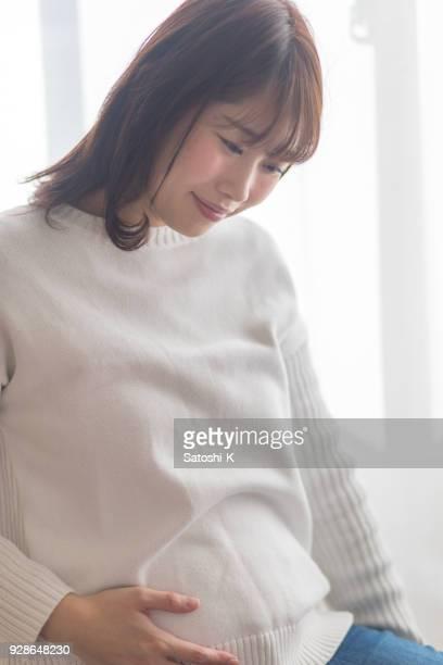 妊娠中のお腹を持つ女性 - 若い女性一人 ストックフォトと画像