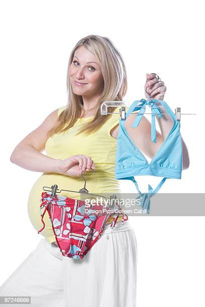 pregnant woman holding bikini - skimpy bathing suits stock pictures, royalty-free photos & images