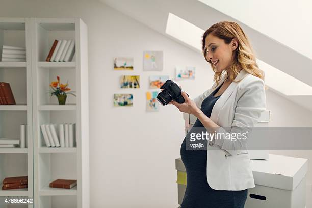 Pregnant Woman Holding Digital Camera and Working In Her Office.
