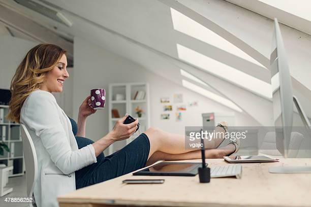 Enceinte femme tenant un appareil photo numérique et de travail dans son bureau.