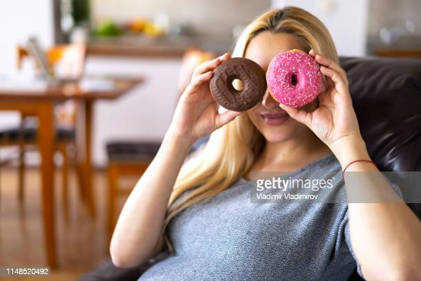 pregnant woman holding donuts and hiding - fat people eating donuts stock pictures, royalty-free photos & images