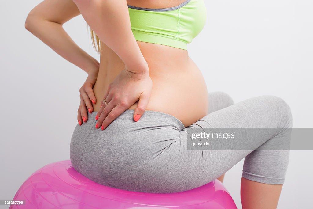 妊娠中の女性彼女の背中をに座っているメディシンボールを : ストックフォト
