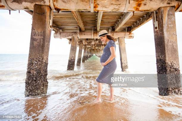 pregnant woman holding her belly - maternity wear stock pictures, royalty-free photos & images