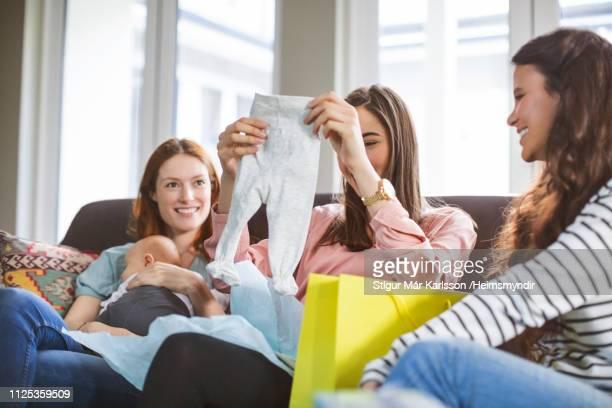 pregnant woman holding pants amidst female friends - pantaloni foto e immagini stock