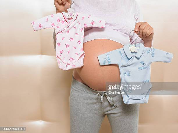 Pregnant woman holding pink and blue babygrows, mid section