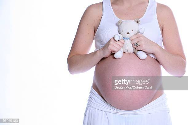 Pregnant woman holding teddy bear over bare belly