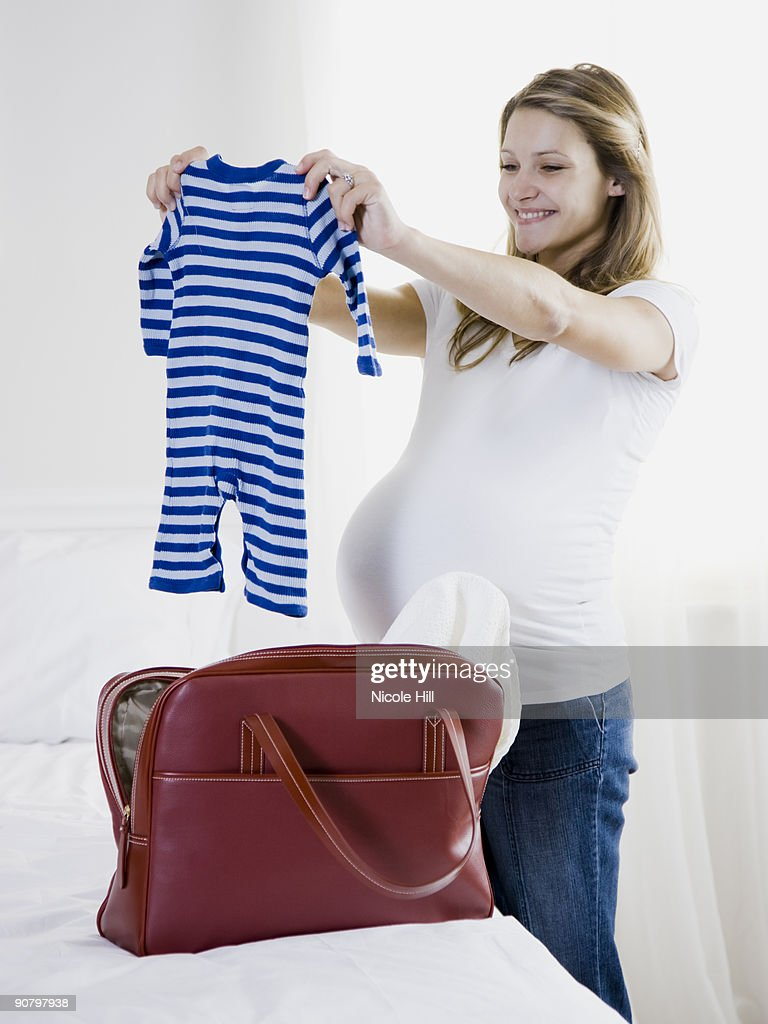 pregnant woman holding up baby clothing : Foto de stock