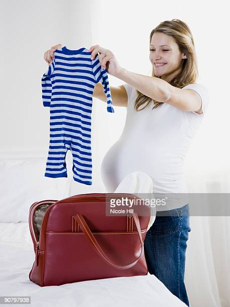 pregnant woman holding up baby clothing